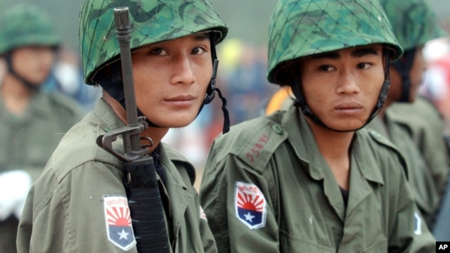 Two young Karen soldiers guard his jungle camp of Mi Aye Bo in Burma's Karen state near the Thai border during a Karen New Year celebration, December 23, 2003.