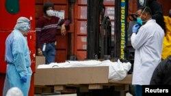 Zdravstveni radnici bolnice u Bruklinu utovaruju posmrtne ostatke u hladnjaču, koja služi kao privremena mrtvačnica (Foto: AP/John Minchillo)