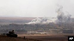 9일 터키에서 바라본 시리아 접경도시 코바니에서 ISIL을 겨냥한 미군 주도의 공습으로 연기가 피어오르고 있다. 터키는 ISIL이 코바니 주변을 장악하자 국경에 탱크부대를 배치했다.