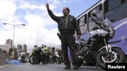 Un policía dirige el tránsito cerca del cuerpo de un hombre que fue asesinado en plena vía, en Caracas.