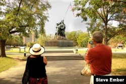 Two visitors from Canada take photos of the Iwo Jima Statue