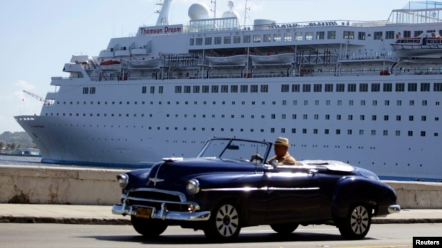 FILE - A man drives his convertible car beside the Maltese-flagged 'Thomson Dream' cruiser docked at Havana's port.