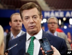 FILE - In this July 17, 2016, file photo, then-Trump Campaign Chairman Paul Manafort talks to reporters on the floor of the Republican National Convention at Quicken Loans Arena in Cleveland as Rick Gates listens at back left.