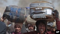 Bangladeshis, who used to work in Libya and fled the unrest in the country, carry their belongings as they arrive in a refugee camp at the Tunisia-Libyan border, in Ras Ajdir, Tunisia, March 9, 2011. (AP Image)