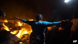 Seorang pedagang mengamati api yang tengah melalap barang-barang miliknya dalam kebakaran pasar di kawasan Petionville, tidak jauh dari ibu kota Haiti, Port-au-Prince, Minggu (20/11)
