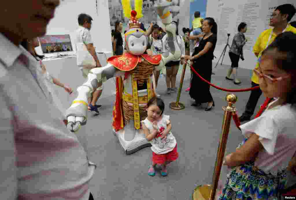 ژست دختر بچه در کنار ربات کپی شده از شخصیت فیلم پادشاه میمون در کنفرانس جهانی ربات در چین