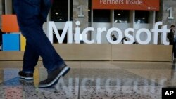 FILE - A man walks past a Microsoft sign set up for the Microsoft Build conference at Moscone Center in San Francisco, April 28, 2015.