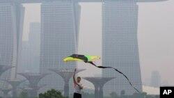 Seorang pria menerbangkan layang-layang di tengah hari berkabut asap di Singapura (10/9). (AP/Ng Han Guan)