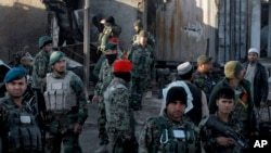 FILE - Afghan security forces inspect damages after clashes between Taliban fighters and Afghan forces in Kandahar, Afghanistan, Dec. 9, 2015. An overnight Taliban attack in Kandahar province killed 11 government soldiers, an Afghan Defense Ministry statement said Tuesday.