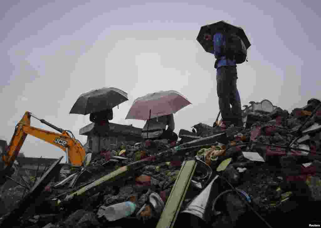 People holding umbrellas gather in the rain on the rubble of a collapsed residential building on the outskirts of Mumbai, India, June 21, 2013.