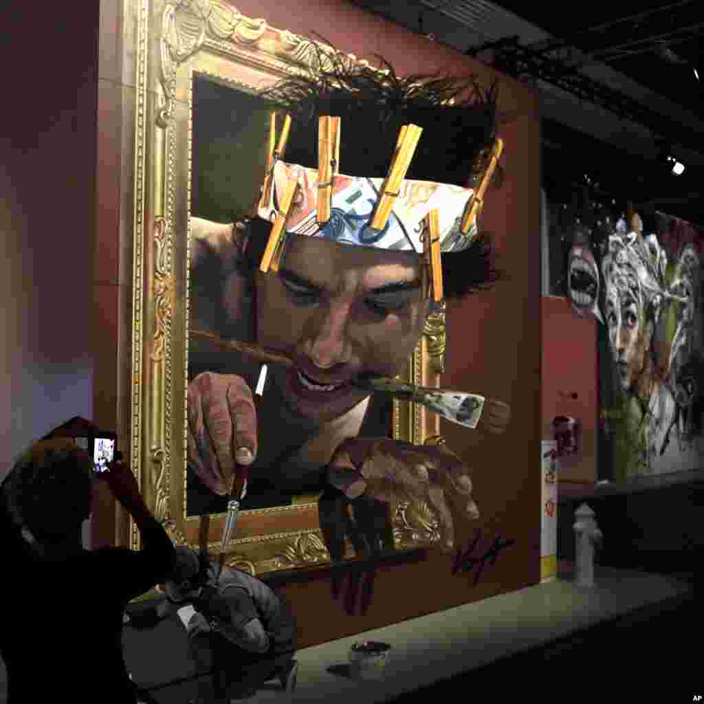 A woman takes pictures of a work by Mexican artist Juandres Vera at the Magic City 'The Art of the Street exhibition' in Munich, Germany.