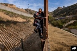 A Honduran migrant grabs his son as they climb the U.S. border fence before jumping into the U.S. to San Diego, Calif., from Tijuana, Mexico, Dec. 22, 2018.