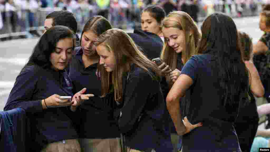 A group of Catholic school girls look at their phones as they wait on the route that Pope Francis will take later in the day near St. Patrick's Cathedral in New York September 24, 2015.