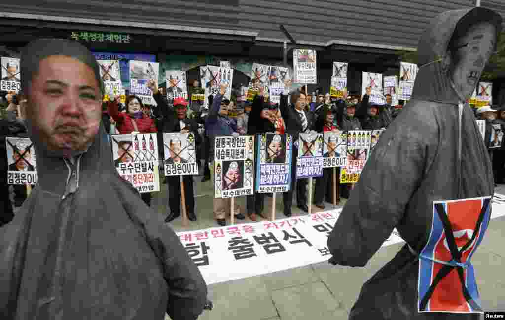 Anti-North Korean protesters chant slogans in front of effigies of North Korean leader Kim Jong Un (L) and his father, the late leader of the North Kim Jong Il in central Seoul, April 15, 2013.