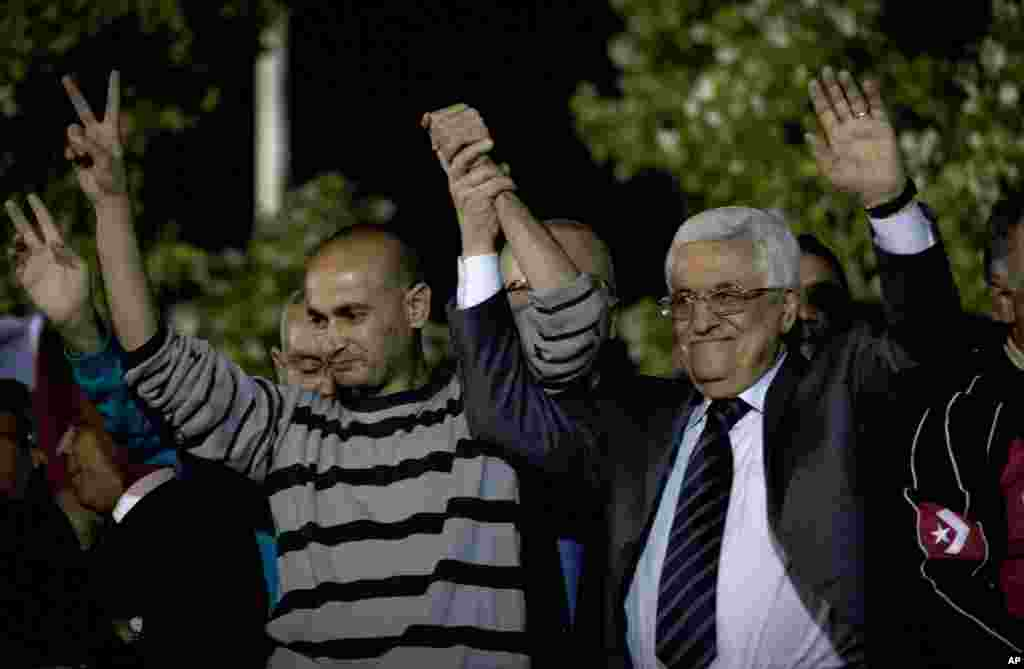 Palestinian President Mahmoud Abbas holds the hand of a freed prisoner during a welcome ceremony at the Palestinian Authority headquarters, in the West Bank city of Ramallah, Oct. 30, 2013.