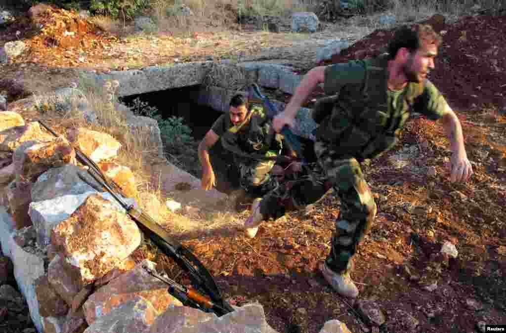 Dua tentara anggota Lasykar Pembebasan Suriah - dari kelompok Brigade Farouq - melakukan latihan militer di Sarmada, dekat provinsi Idlib (9/7).