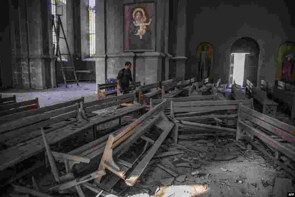 A man walks inside the Ghazanchetsots (Holy Saviour) Cathedral in the historic city of Shusha, that was hit by a bomb as fighting between Armenian and Azerbaijani continues over the disputed Nagorno-Karabakh province.