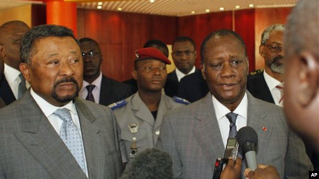 Ivory Coast's internationally-recognized President, Alassane Ouattara, right, addresses journalists following a meeting with African Union commission chairman Jean Ping, left, at the Golf Hotel in Abidjan, Ivory Coast, March 5, 2011