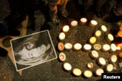 A photo of music icon John Lennon and peace sign made of candles sit on the pavement near Lennon's star during a gathering of fans and supporters in front of the Capitol Records building on the Hollywood Walk of Fame in Hollywood, California December 8, 2005.