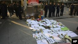 Security guards stand near protest banners and flowers laid outside the headquarters of 'Southern Weekly' newspaper in Guangzhou, Guangdong province, China, January 7, 2013.
