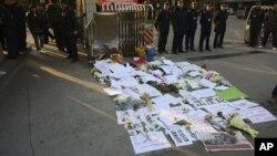 警察在擺放菊花和支持標語的《南方周末》報刊門前站崗確。