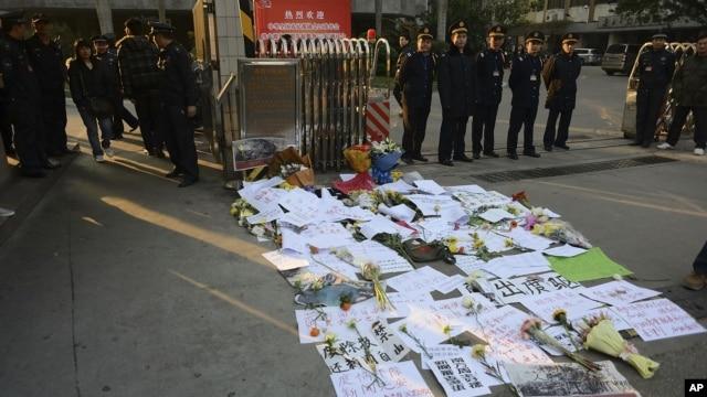 Nhân viên bảo vệ đứng gần các biểu ngữ phản đối và hoa bên ngoài trụ sở của Tuần báo Nam Phương ở tỉnh Quảng Ðông, ngày 7/1/2013.