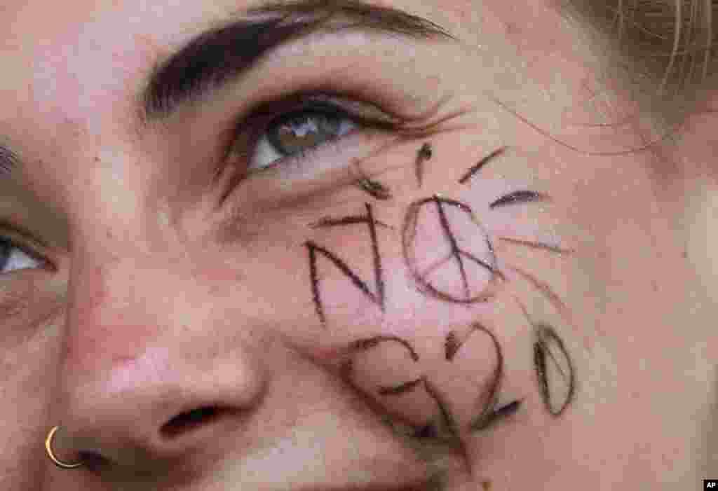 """一个行反对20国集团汉堡峰会的示威者微笑,脸上写着""""不要G20""""(2017年7月8日)。"""