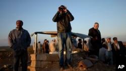 Turkish Kurds watch clashes between Syrian Kurdish fighters and Islamic State militants close to the Turkey-Syria border near Suruc, Turkey, Sept. 28, 2014.
