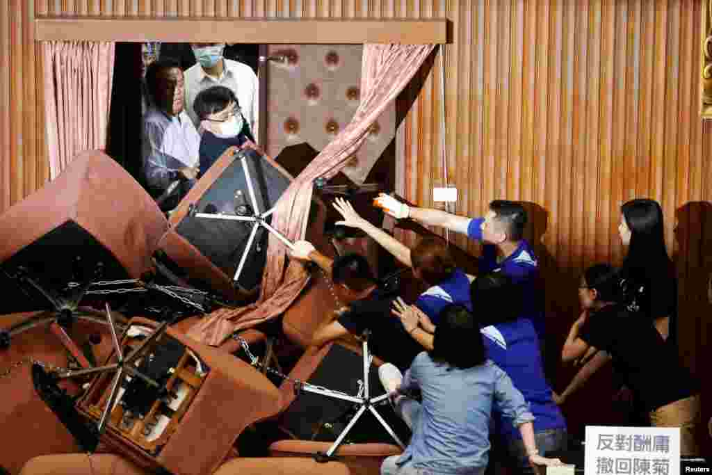 Lawmakers from Taiwan's ruling Democratic Progressive Party (DPP) argue with lawmakers from the main opposition Kuomintang (KMT) party, in Taipei, Taiwan.