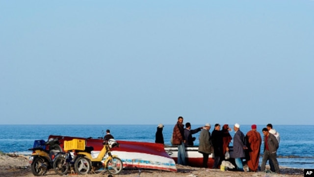 Tunisian people stand at the seaside in coastal town Zarzis in southeastern Tunisia, February 18, 2011