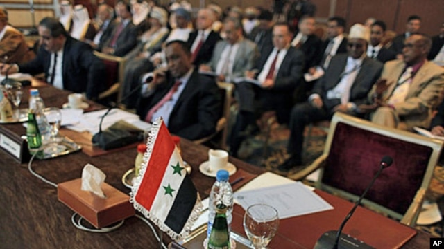 "The Syrian flag and a sign in Arabic that reads, ""the Syrian Arabic Republic,"" is seen in front of the empty chair of the Syrian representative during the Arab League Syria Group and foreign ministers meeting in Cairo, Egypt Sunday, February 12, 2012."