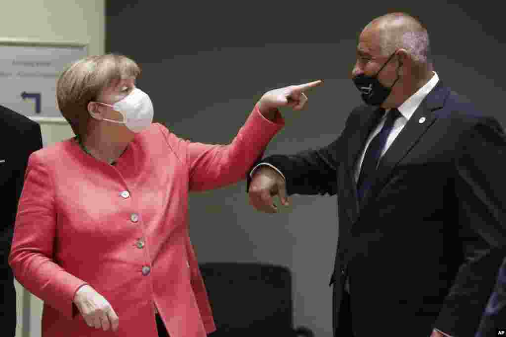 German Chancellor Angela Merkel, left, speaks with Bulgaria's Prime Minister Boyko Borissov during a round table meeting at an EU summit in Brussels, Friday, July 17, 2020. (Stephanie Lecocq, Pool Photo via AP)
