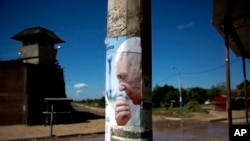 FILE - A poster of Pope Francis covers a lamppost outside Palmasola prison where the pontiff visited inmates in Santa Cruz, Bolivia, July 10, 2015.