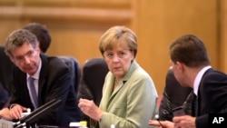 德国总理默克尔(中)7月7日在北京会晤中国总理李克强时与代表团成员交换意见