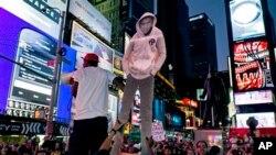 Potongan gambar Trayvon Martin dibawa para pendukungnya dalam aksi protes di Times Square, New York, Minggu (14/7), seusai diumumkannya putusan dewan juri pengadilan Florida tentang pembebasan George Zimmerman.
