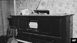This girl did not have to anything but watch the piano roll turn on her player piano at her home in New Jersey in 1940.
