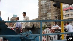 Citizens & police officers gather at the site of an explosion targeting a traffic police booth that injured two police officers, near al-Galaa bridge, in central Cairo, Egypt, Tuesday April 15, 2014.