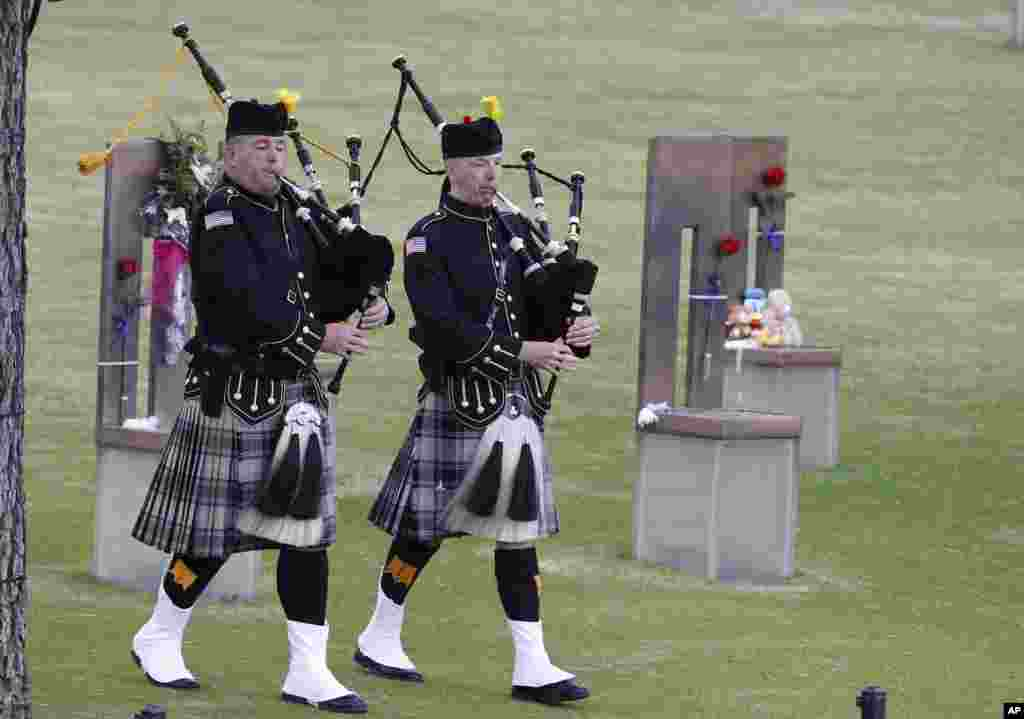 Bagpipers walk through the Field of Empty Chairs at the Oklahoma City National Memorial at the start of ceremonies to commemorate the 20 year anniversary of the Oklahoma City bombing in Oklahoma City, April 19, 2015.