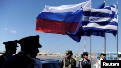 FILE - Greek police and army officers stand by Greek, Russian and EU flags as they wait for the arrival of Russian President Vladimir Putin in Athens airport, May 27, 2016.