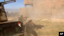 In this still image taken from video soldiers fire towards a target in Tikrit, Iraq, March 11, 2015.