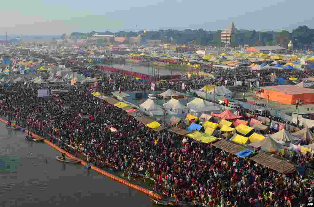 Hindu devotees arrive to take a holy dip at Sangam, the confluence of the rivers Ganges and Yamuna and mythical Saraswati, during the auspicious bathing day of Mauni Amavasya at the annual Magh Mela festival in Allahabad, India.