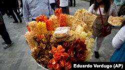 In this July 5, 2016 file photo, a street vendor sells fried snack food in Mexico City. (AP Photo/Eduardo Verdugo, File)