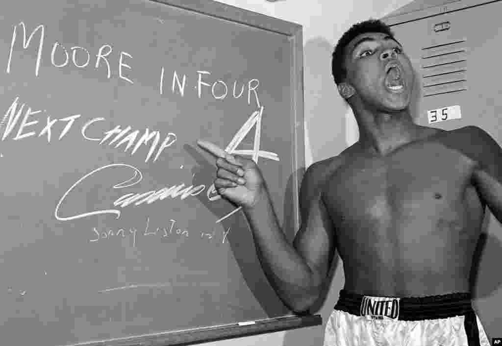 រូបឯកសារ៖ នៅក្នុងរូបថតកាលពីថ្ងៃទី១៥ ខែវិច្ឆិកា ឆ្នាំ១៩៦២ កីឡាប្រដាល់ទម្ងន់ធ្ងន់វ័យក្មេង Cassius Clay ដែលបន្ទាប់មកបានផ្លាស់ប្តូរឈ្មោះទៅជា Muhammad Ali ចង្អុលទៅកាន់សញ្ញានៅលើក្តារខៀនដីសនៅក្នុងបន្ទប់ផ្លាស់សំលៀកបំពាក់ មុនពេលការប្រកួតជាមួយនឹងកីឡាករ Archie Moore ក្នុងក្រុង Los Angeles ដោយធ្វើការព្យាករណ៍ថា លោកនឹងវាយកីឡាករ Moore ឲ្យសន្លប់នៅទឹកទីបួន។