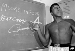 FILE - Young heavyweight boxer Cassius Clay, who later changed his name to Muhammed Ali, points to a sign he wrote on a chalk board in his dressing room before his fight against Archie Moore in Los Angeles, in this Nov. 15, 1962 file photo.