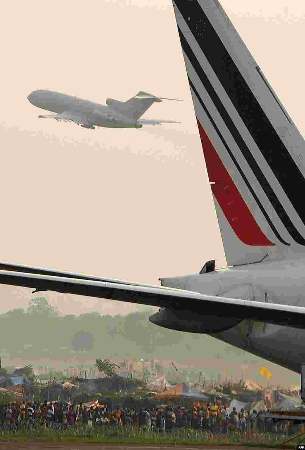 Một phi cơ của hãng Air-France đậu trên phi cảng Nangui khi một phi cơ khác cất cánh gần một trại dành cho những người dời cư ở thủ đô Trung Phi.