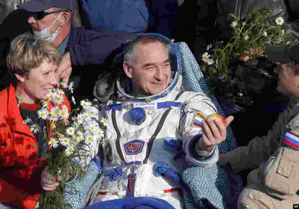 Russian cosmonaut Alexander Skvortsov holds a traditional apple after landing in the Soyuz TMA-12M space craft near the city of Zhezkazgan, Kazakhstan, Sept. 11, 2014.