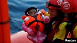 Una tripulante del MV Open Arms, el barco de búsqueda y rescate de Proactiva Open Arms, sostiene a un bebé migrante al pasarlo a una tripulante del MV Aquarius un barco de búsqueda y rescate administrado por SOS Mediterranee y Médicos Sin Fronteras en el mar Mediterráneo frente a las costas de Libia el domingo, 16 de diciembre de 2017.