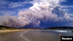 Smoke from a bushfire billows over beach goers at Carlton, about 20 kilometers (12 miles) east of Hobart, Australia, January 4, 2013.