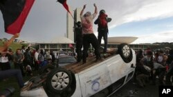 Protesters stand on an overturned car outside Congress where senators later voted in support of a spending cap bill in Brasilia, Tuesday, Nov. 29, 2016.