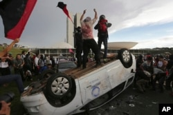 FILE - Protesters stand on an overturned car outside Congress where senators planned to vote on a spending cap bill and the lower Chamber of Deputies was considering controversial anti-corruption legislation, in Brasilia, Brazil, Nov. 29, 2016.